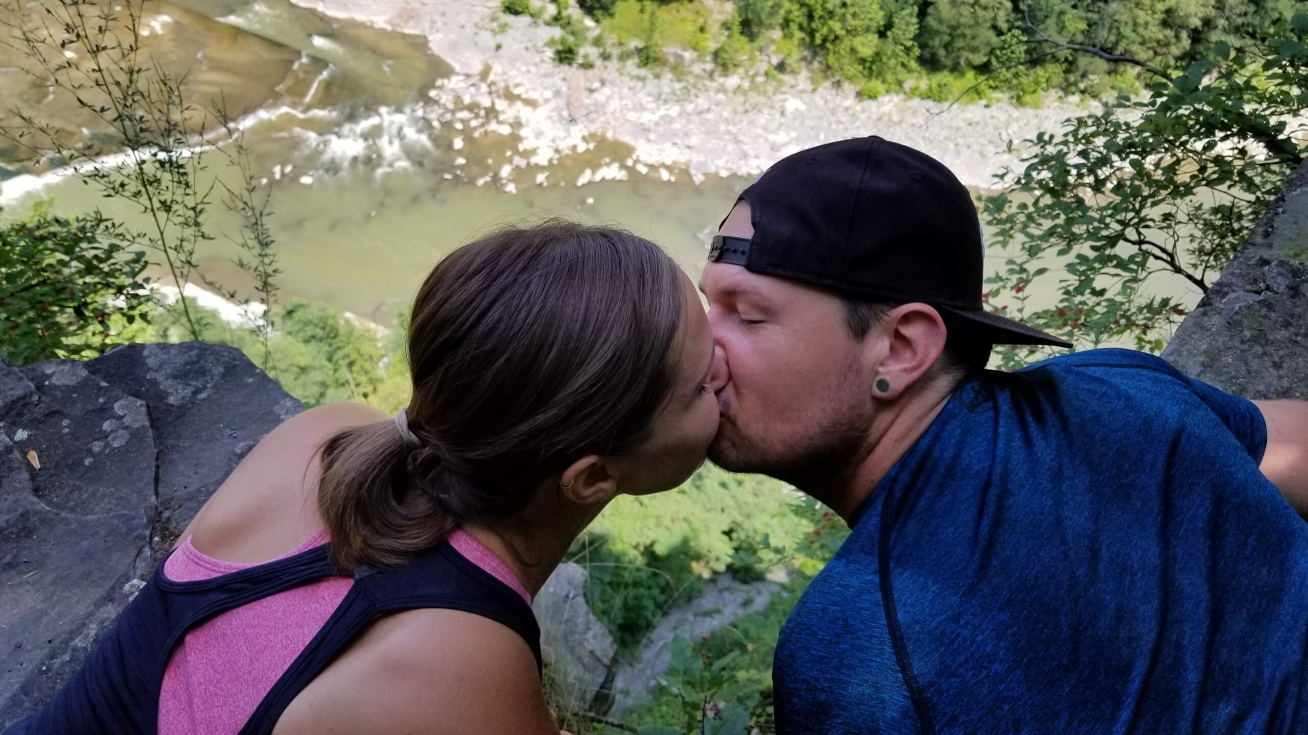 Dennis and Liz kissing over ledge and river