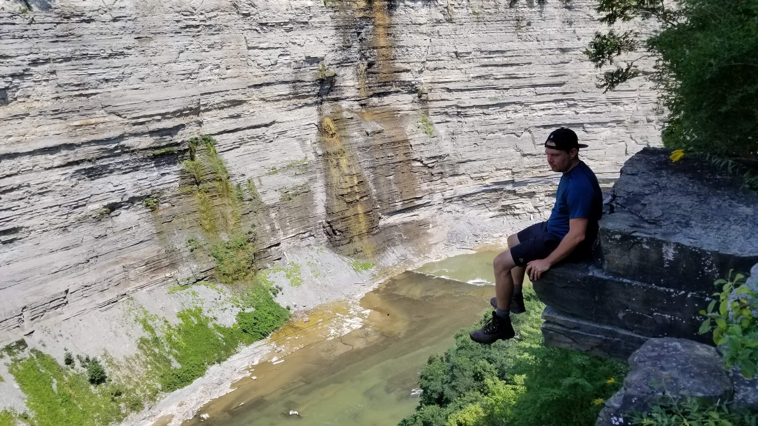 Dennis sitting on high Ledge over river