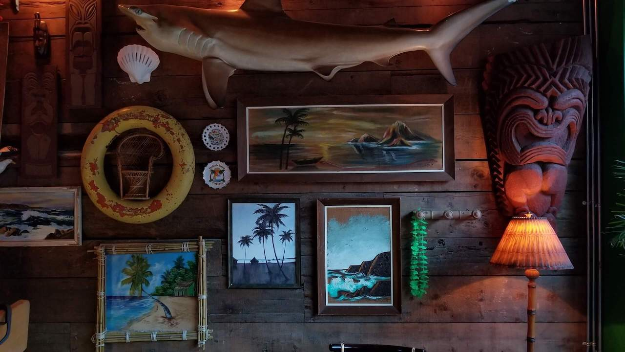 Tiki Bar wall with shark tiki head and pictures of ocean
