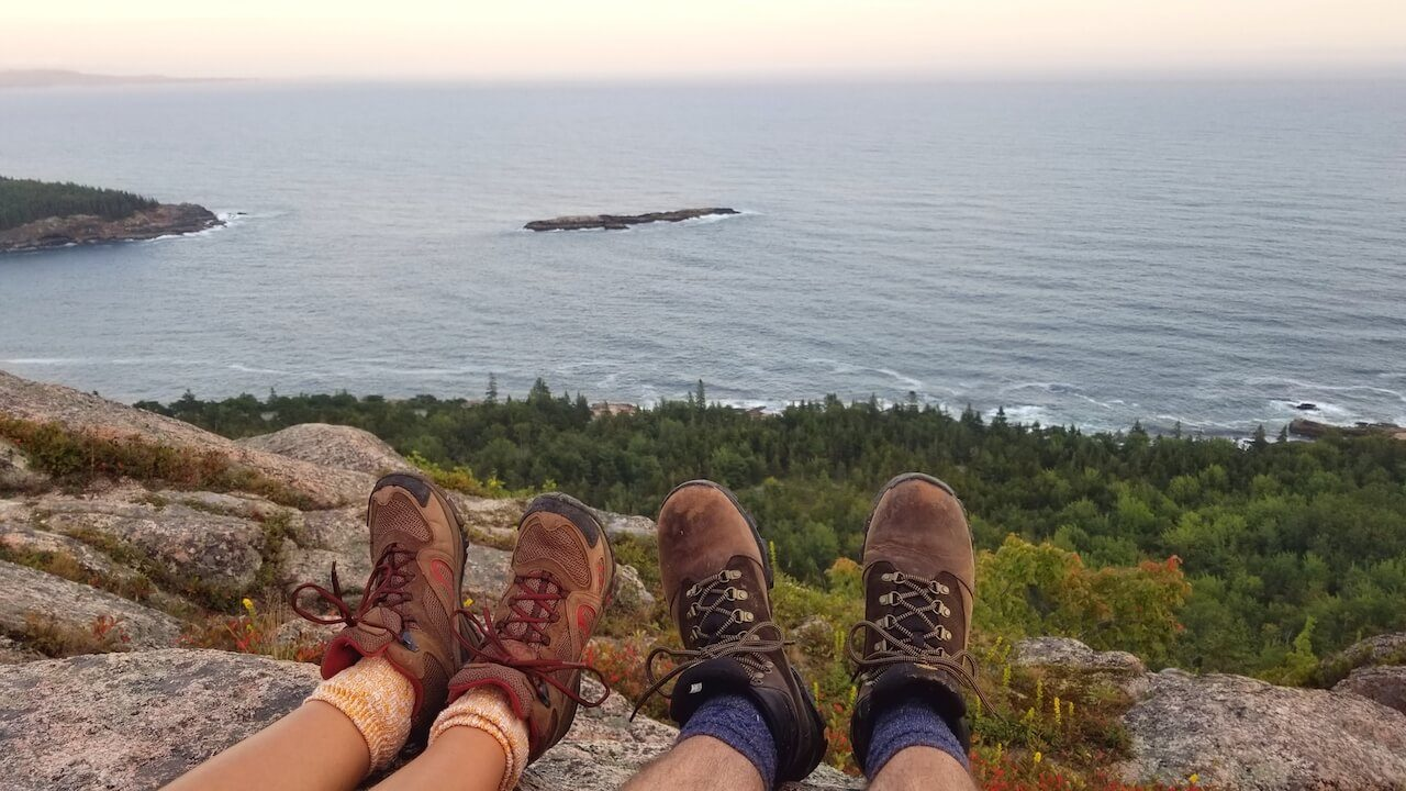 Two pairs of hiking boots over mountain cliff with ocean and trees Acadia National Park
