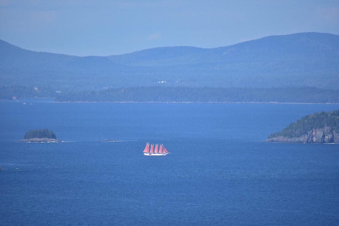 Sailboat with four red sails in Maine mountains behind