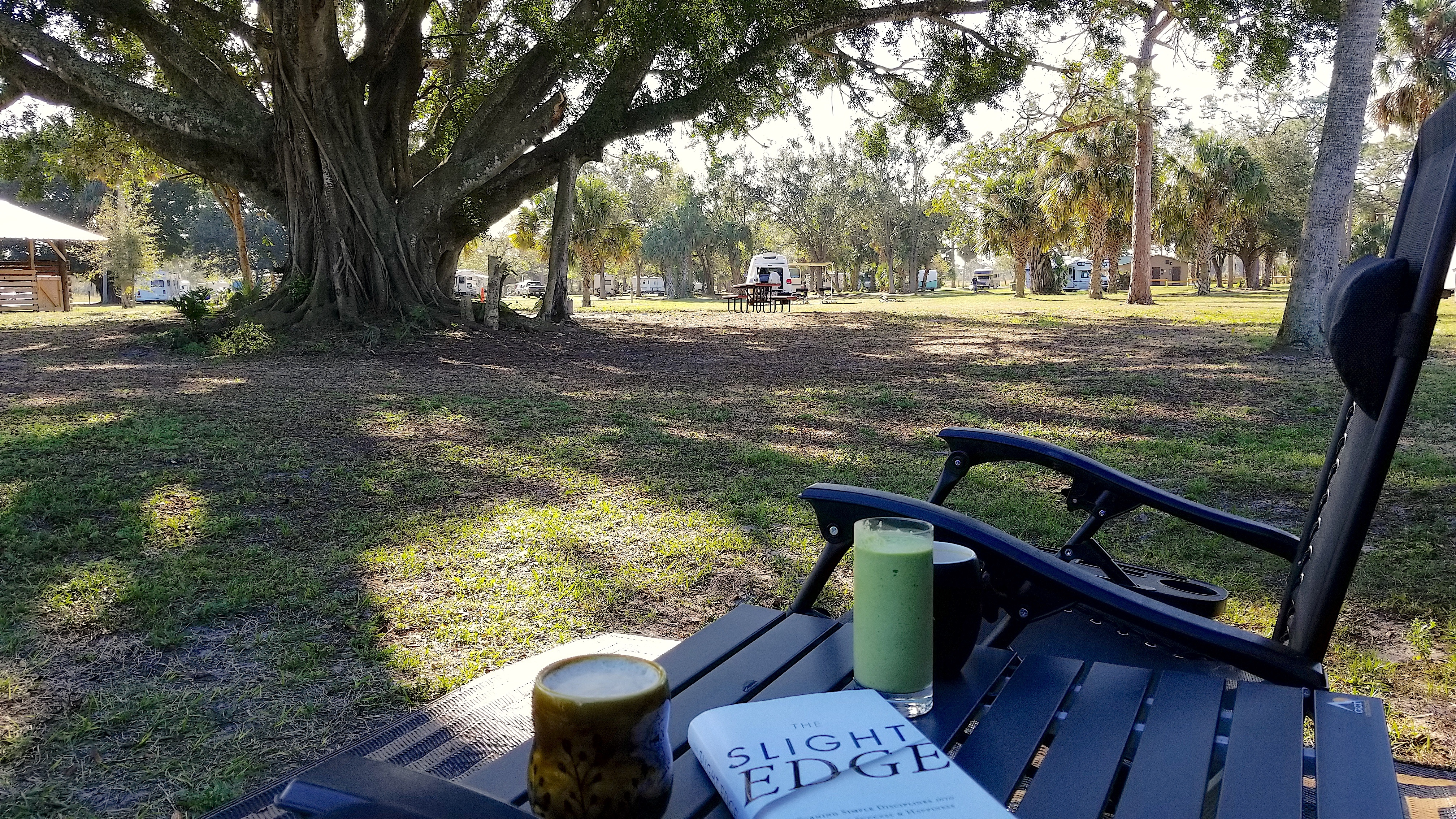 Camping with Smoothie, Coffee, book, and patio chairs with tree