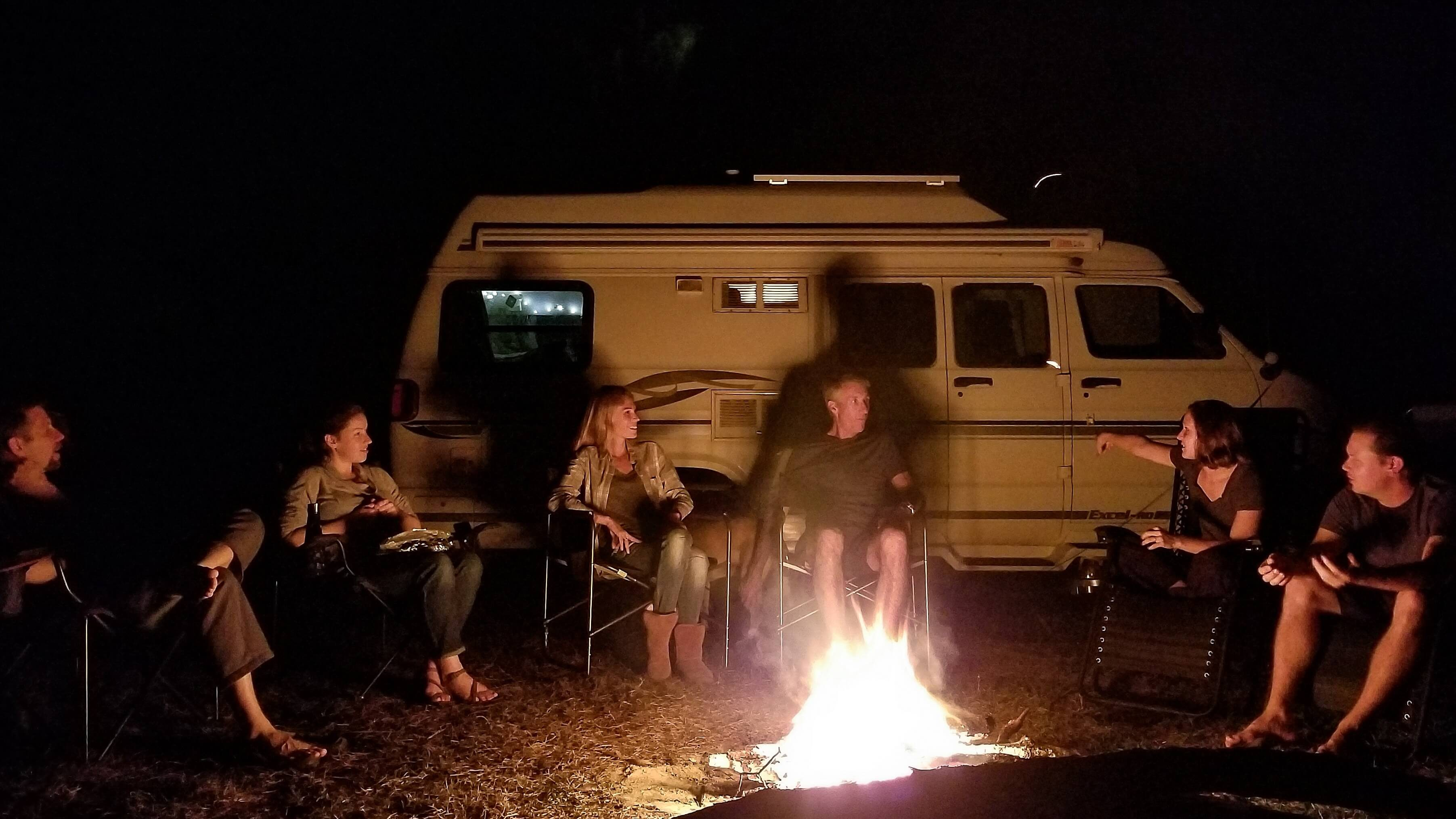 People sitting around campfire in front of camper van